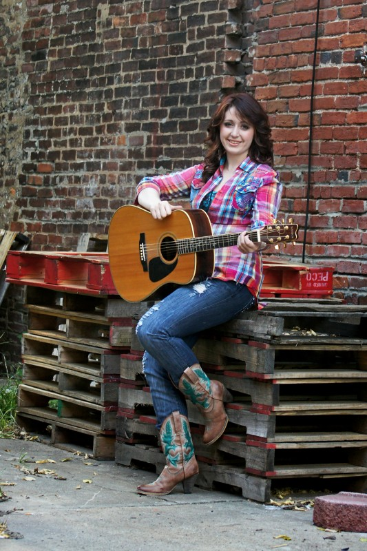 Alexes Aiken in boots on pallets